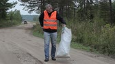 utilization : Man with cell phone and bag of plastic bottles on the road in forest