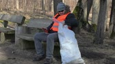 utilization : Tired man with bag of plastic bottles on bench in the park
