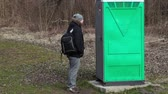 movable : Man waiting near green portable toilet in the park Stock Footage