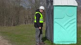 movable : Worker waiting near portable toilet