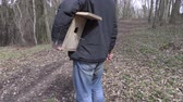 vysedět : Man with birdhouse and hammer on path in the park