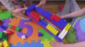toys : Mother help daughter build house from toy bricks