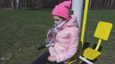 children playground : Little girl sitting on the training machine and drinking water