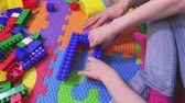 дома : Mother help daughter fix toy bricks
