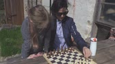 gry : Mother teaching daughter playing chess