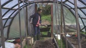 gardens : Woman take soil out from wheelbarrow Stock Footage