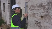 измерительный : Female builder checking wall with spirit level