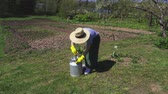 farming equipment : Woman with metallic bin in garden
