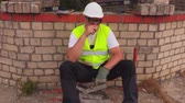 social worker : Construction worker smoking near unfinished building