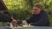 satranç : Two men near chessboard at outdoor Stok Video