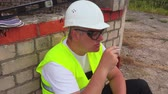 рабочий : Construction worker smoking near brick wall