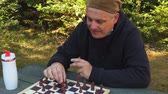zafer : Man smoking and playing chess Stok Video