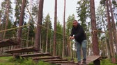 obstacle course : Afraid man walking on rope bridge in park Stock Footage