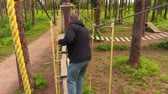 obstacle course : Man walking on cables between trees Stock Footage