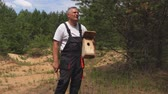 защита : Man with hammer and bird box Стоковые видеозаписи