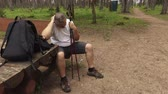 пеший туризм : Tired hiker with walking sticks resting in park on bench