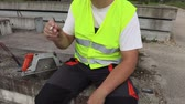 курение : Camera focuses on smoking construction worker