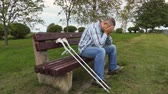 assistência : Sad disabled with crutches in park on bench