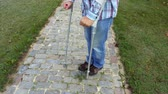 gyógyszerek : Man with crutches on cobbled path Stock mozgókép