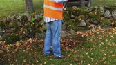 грабли : Man collect autumn leaves near stone wall fence