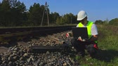 munkatársa : Engineer near railway with laptop check the electronics relay Stock mozgókép
