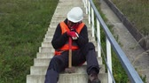 рабочий : Lazy worker with hammer relax on concrete stairs