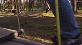 Camera follows man legs on rope bridge in park trees Dostupné videozáznamy