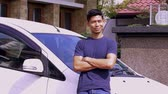 malaio : Mid adult man leaning on his car and smiling