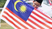 religious symbols : Malaysian boy holding National flag Stock Footage