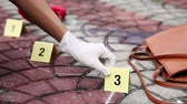handbag : Investigator placing down evidence card at crime scene Stock Footage