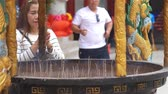 místní : Woman putting joss stick in incense pot and prays