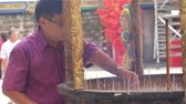kulturális : Person putting joss stick in incense pot and prays Stock mozgókép