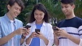 технология : Three young adults using their smartphones Стоковые видеозаписи