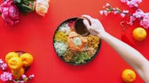 измельченный : Pouring condiments onto the yee sang