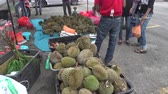 asiáticos : Asians buying Durians at a roadside stall. Durian is a king of fruit that have a notorious aroma but tastes like a rich custard highly flavoured with almonds.