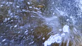 Water from fountain spraying against rock in slow motion, vibrant summer look.
