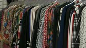 Clothing on hangers at a market stand Стоковые видеозаписи