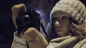 momentka : girl photographer shooting outdoors on snow winter night ligh park. Dostupné videozáznamy