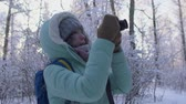momentka : Beautiful young woman in winter clothing, mittens and wool hat photographing snowy forest by a knitted camera