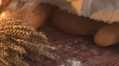 vajas : handmade tasty bread lying on burlap on the wooden table with flour, wheat and ears of wheat. Stock mozgókép