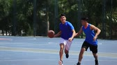 дриблинг : asian young adults playing basketball on outdoor court.