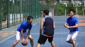 tática : asian young adults playing basketball on outdoor court.