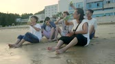 cimborák : young asian adults sitting relaxing on beach and drinking beer to a toast.