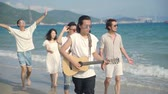 lungomare : group of young asian adults men and women having fun walking singing on beach