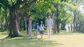asian family with two children walking hand in hand having fun in park