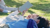 beautiful little asian girl and boy sister and brother lying on grass reading a book together in park Стоковые видеозаписи