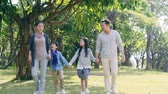 asian family with two children having fun walking hand in hand in park