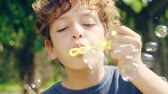 dez : close-up shot of a 10 year-old italian boy having fun blowing bubbles outdoors in a park Vídeos