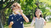 two children one italian on chinese having fun blowing bubbles outdoors in a park Стоковые видеозаписи
