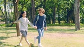 dez : little caucasian boy and asian girl holding hands walking in woods in park